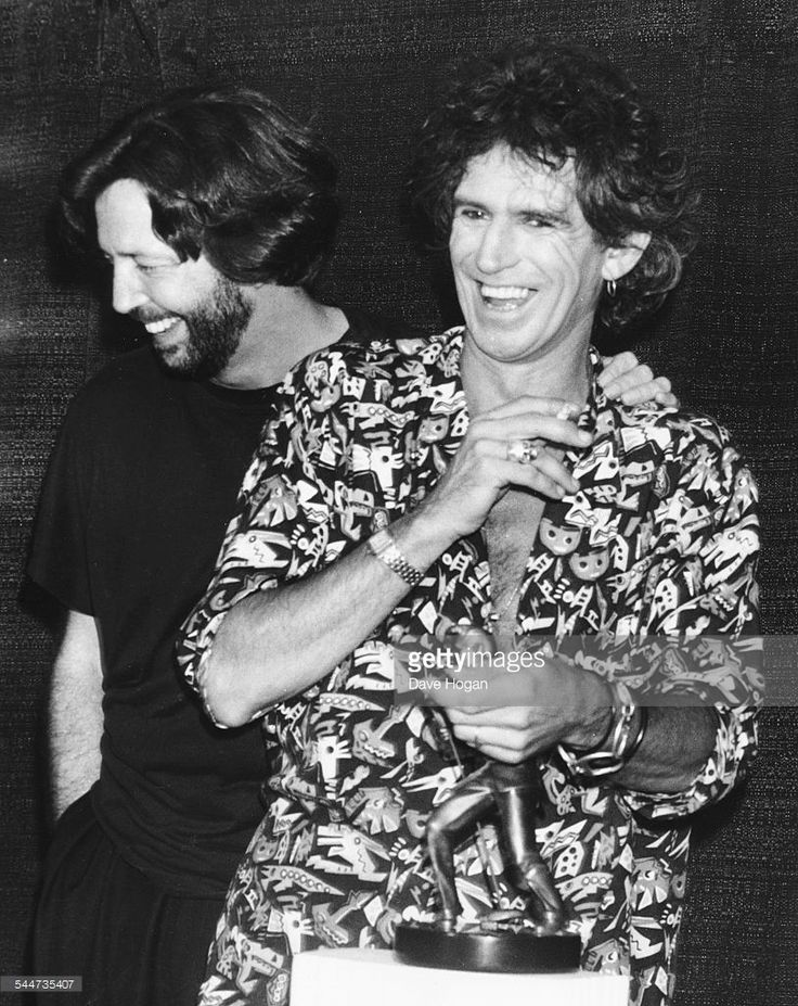 Musicians Eric Clapton (left) and Keith Richards laughing together at the International Rock Awards, June 2nd 1989.