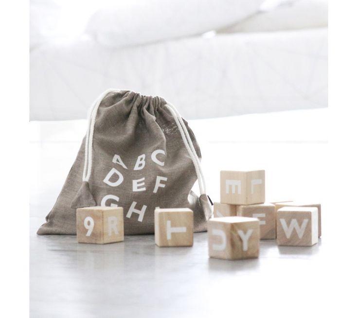 Smukke klodser med hvide bogstaver og tal på lyst træ, som kan bruges til at...