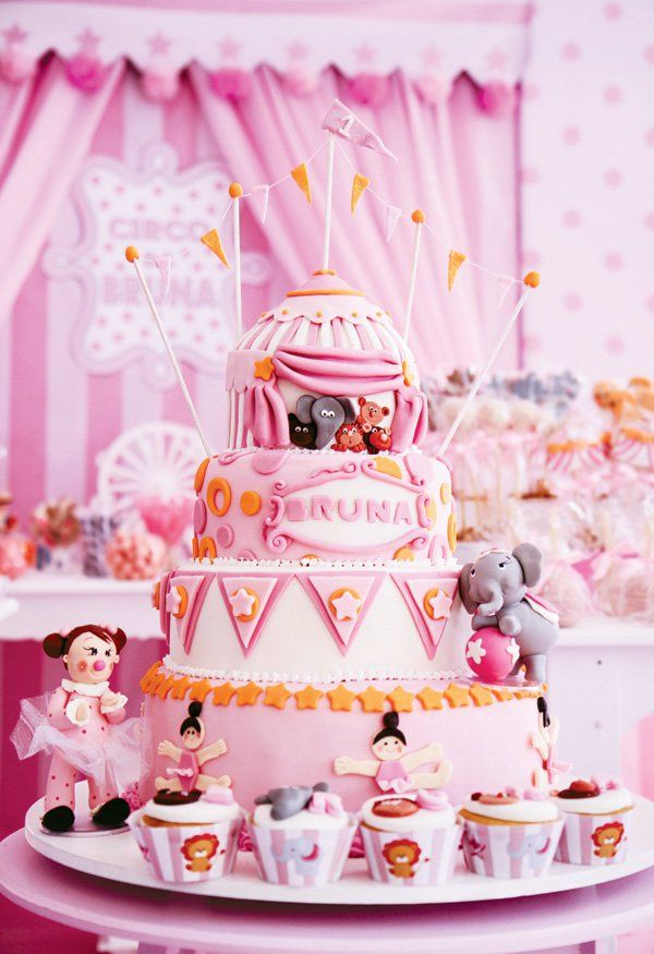 A Circus First Birthday Party with carousel horse balloon, pink ballerina statues, circus animal desserts, candy concession + pink circus tent birthday cake