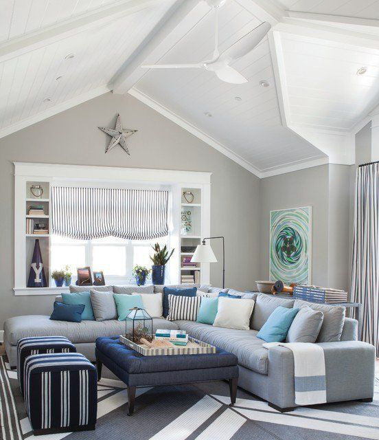 beige/sand walls, grey couch with blue cushions