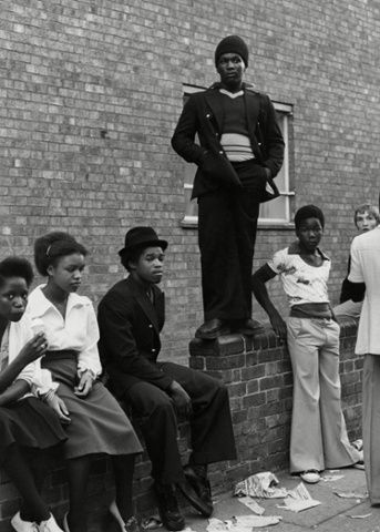 Group of teenagers sitting and standing on a wall, Notting Hill Carnival London, 1975