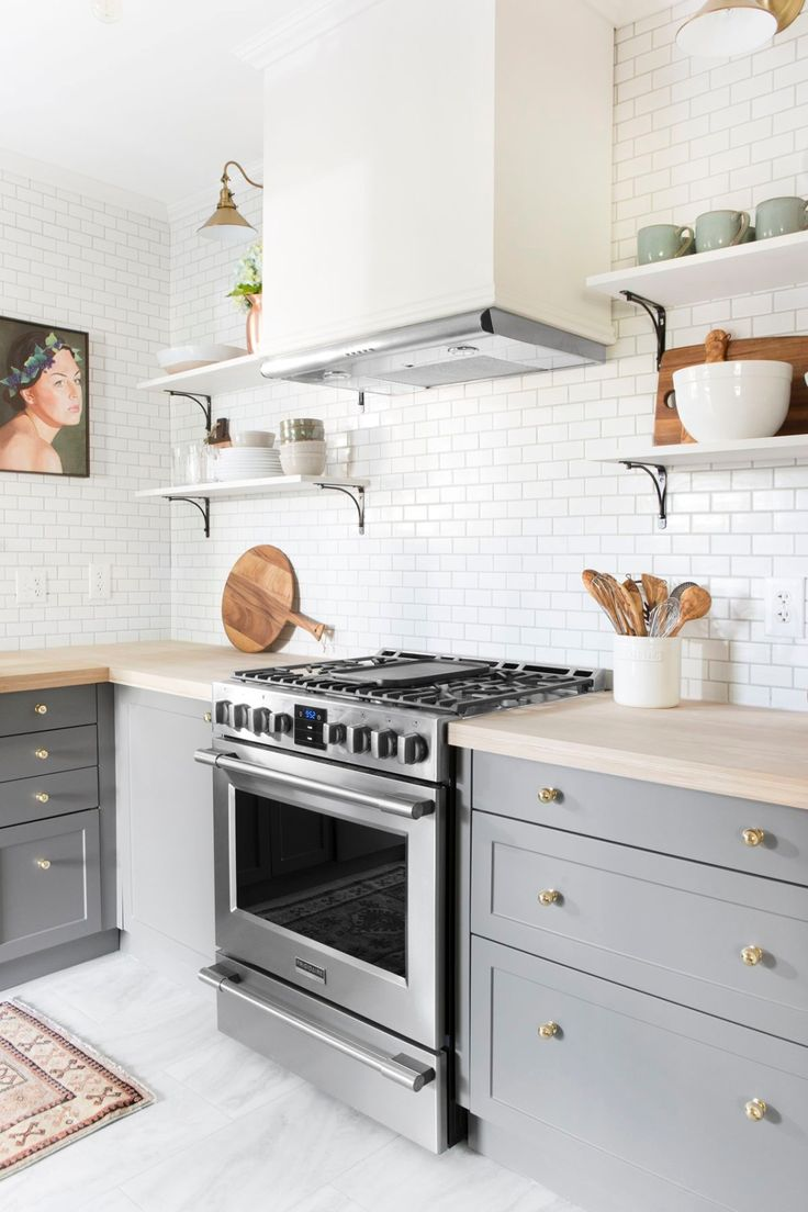 Beautiful gray and white kitchen with open shelves, subway tile backsplash and simple Shaker cabinets.