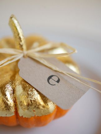 These mini pumpkins are half painted in gold paint -- use them as a place card setting for an elegant way to decorate a dinner party