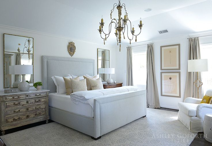 Ashley Goforth Design - bedrooms - pressed botanical prints, botanical prints, botanical art, art between windows, linen drapes, linen curtains, vaulted tray ceiling, dark hardwood floors, neutral print rug, neutral medallion rug, medallion print rug, gray bed, gray upholstered bed, white bed linens, beige hotel bedding, beige pillows, patterned beige pillow, distressed nightstand, french nightstand, wooden nightstand, taupe table lamp, ceramic taupe table lamp, art over headboard, mirrors…