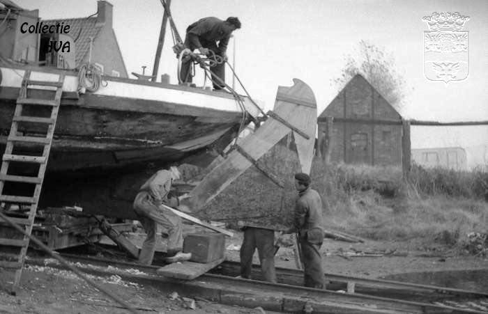 De mannen van de werf hangen een gerepareerd roer op / replacing a repaired rudder