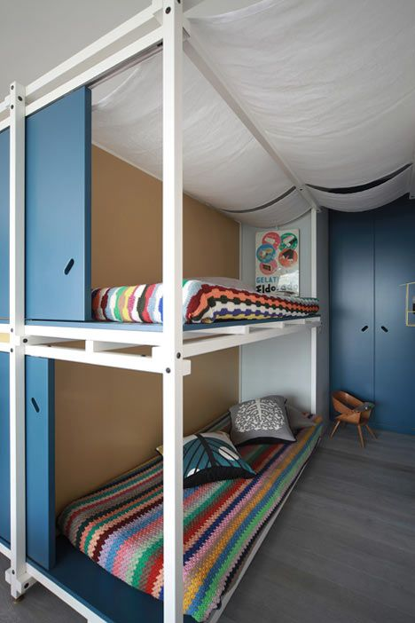 Sliding blue and yellow walls hide the sleeping and storage spaces in this 1970s-inspired beach apartment in the south of France