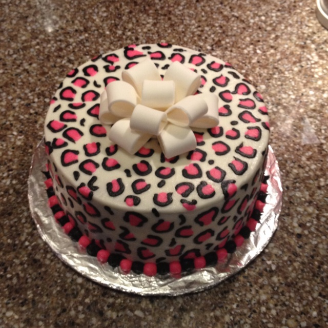Hot pink cheetah print cake made with buttercream. Fondant bow on top.