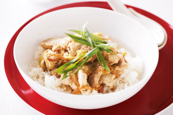 Japanese donburi with soy sauce, sushi rice, tender chicken and sliced green onion.