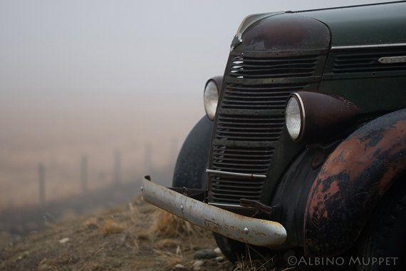 Rusty old International truck parked near a field in the fog