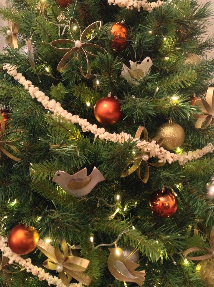Árbol de Navidad con flores hechas con cartón de los rollos de papel higiénico, y palomas cortadas en hojalata de refresco. Guirnalda de palomitas de maíz.