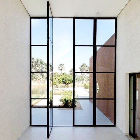 Black glass doors that open to a beautiful landscape! | Designed by Atelier Koe, Photo by Regis L'hostis via @archdaily #atelierkoe #interiordesign