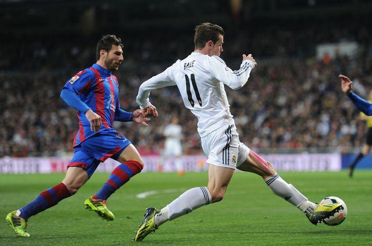 Gareth Bale runs around Nikos Karabelas during the La Liga match between Real Madrid CF and Levante UD at Estadio Santiago Bernabéu on March 9, 2014 in Madrid, Spain.