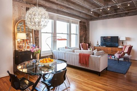 Old factory converted into a trendy loft apartment in downtown Houston by interior designer Kristina Wilson with brick walls, wood floors and large windows.