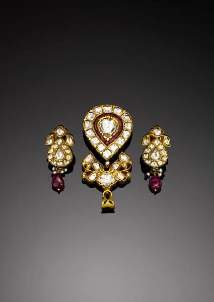 A diamond and ruby-set enamelled gold Pendant with associated pair of Earrings. Northern India, 20th Century of drop-shaped form suspended from a leafy pierced element, the earrings of similar but smaller form, each with floral polychrome enamel decoration on the reverse 6 cm. long max