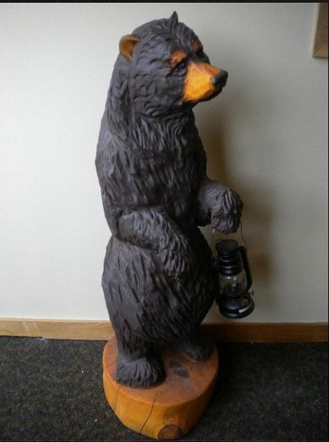 Bear chainsaw carving holding a lantern beautifully