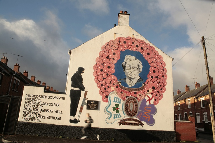 A local teenager runs past this memorial to one of the victims of inter-factional asassination. The poem, by Siegfried Sassoon, written of the 1st World War, provides the irony: thousands have died in Northern Ireland`s `Troubles,` the vast majority, people who had no involvement in paramilitary organisations but were innocent`civilians.` Murals like these still very effectively remind local people of which organisation`s territory their streets fall within.