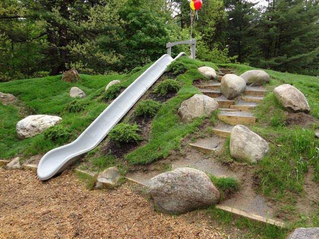 An embankment slide is built into a constructed hill at an elementary school.