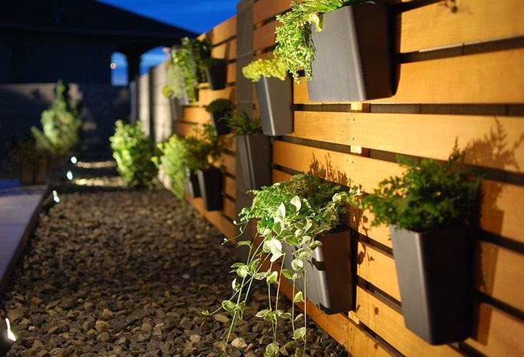 Diy modern wood slat garden wall with hanging planters and