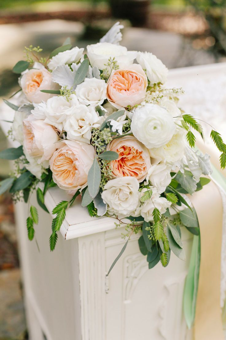 The bridal bouquet will be a loose clutch of ivory garden roses, peachy Juliet garden roses, ivory spray roses, white ranunculus, grey dusty miller, and green seeded eucalyptus wrapped in ivory ribbon with the stems showing