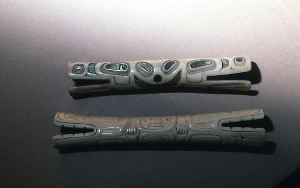 Two soul catchers, one above inlaid with abalone, and of Tsimshian design. Lower one  with greater relief carving, of Haida design.