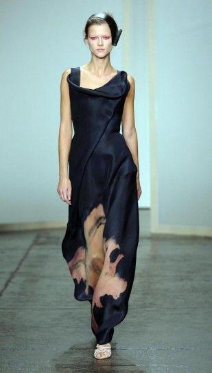 Donna Karan porta la sua eleganza unica in passerella durante la New York Fashion Week. La nuova collezione primavera estate 2013 punta su abiti lunghi, modelli ricercati e sofisticati ai quali la stilista aggiunge grazia e vivacità per mezzo di colori moda e forme particolari. Nella foto abito nero con stampa floreale.