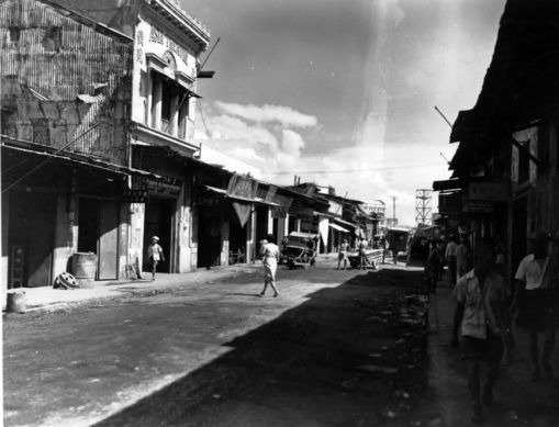 A street scene in the Chinese section of Manila, Philippines, with cars parked along the side of the street. All people are unidentified. Donor: John Paxton