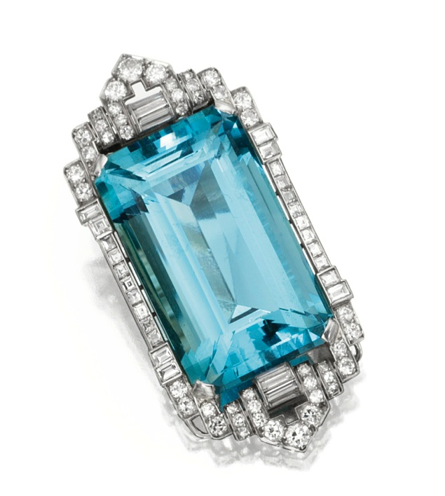 PLATINUM, WHITE GOLD, AQUAMARINE AND DIAMOND CLIP-BROOCH, CIRCA 1930  The emerald cut aquamarine weighing approximately 95.00 carats, framed by round, square-cut and baguette diamonds weighing approximately 4.00 carats.