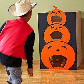 Zielwerfen zu Halloween: Gestalten Sie einen großen Kartong als Kürbispyramide und schneiden Sie unterschiedlich große Löcher hinein, in die nachher die Kinder die Tischtennisbälle werfen sollen.