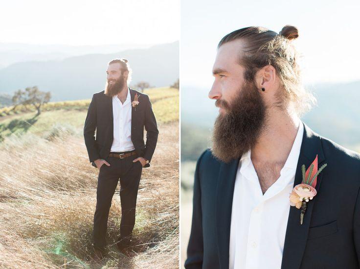 Modern hipster groom with a beard and man bun