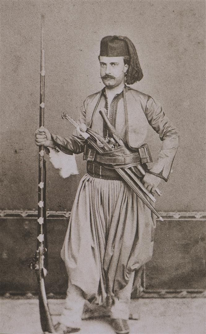 Armed man from Skafia (Crete). Late 19th century, shown holding a rifle and with two pistols (kuber) and a yatagan in his weapons belt (silahlik).
