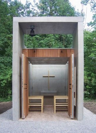 Standing isolated in a clearing in the middle of the park of the old Kolbermoor spinning mill is the Chapel of St. Benedict. Visitors enter the sacred space by passing through a tall entrance portal that contains the chapel`s small bell: the classic image of the church with its bell tower is not abandoned, but rather reinterpreted with a modern spirit.