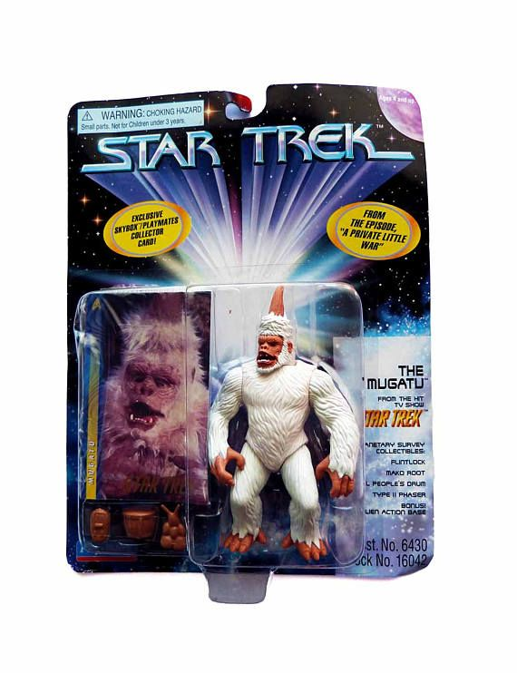 Star Trek 5 Action Figure  Manufacturer: Playmates Character: THE MUGATU  Attributes: The Mugato as seen in the Classic Star Trek episode: A Private Little War.  Asst No. 6430 Stock No. 6436  Circa 1996. Display packaging includes Skybox Playmates Collector Card, Alien Action Base for standing & 4 Planetary Survey Collectibles.  NEW in Original packaging. Corner curling. Otherwise, EXCELLENT. One than one toy? Well consolidate shipping costs. We ship carefully packaged, insured with deliv...