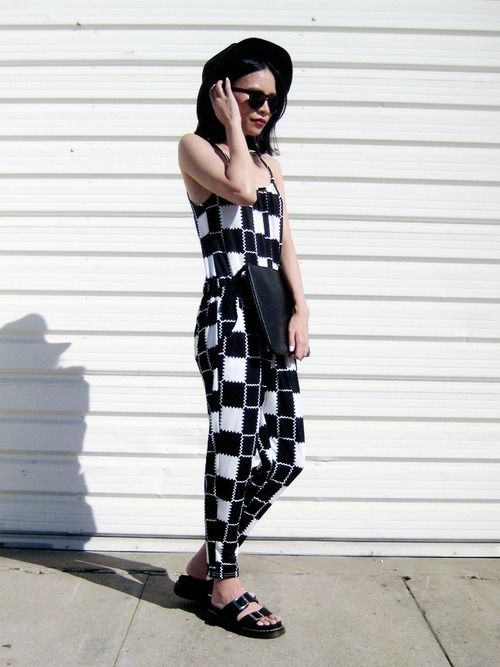 Shop this look for $91:  http://lookastic.com/women/looks/black-clutch-black-and-white-jumpsuit-black-flat-sandals-black-hat/2920  — Black Leather Clutch  — Black and White Plaid Jumpsuit  — Black Leather Flat Sandals  — Black Wool Hat