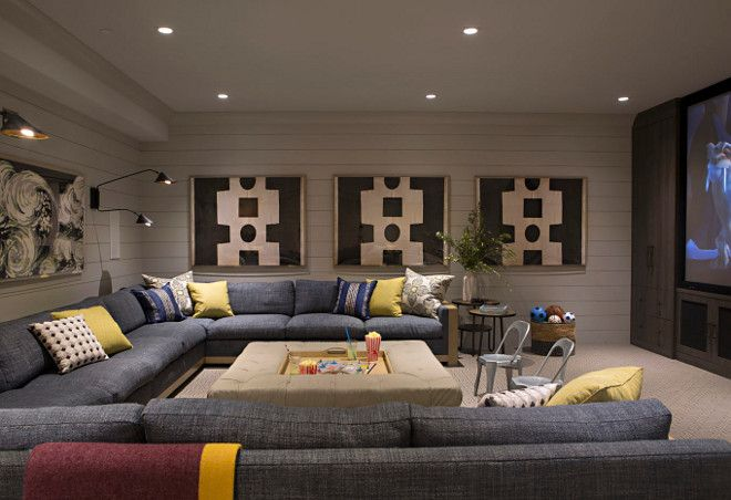 Basement media room with large sectional, ottoman with tray, carpet flooring and shiplap wall paneling.
