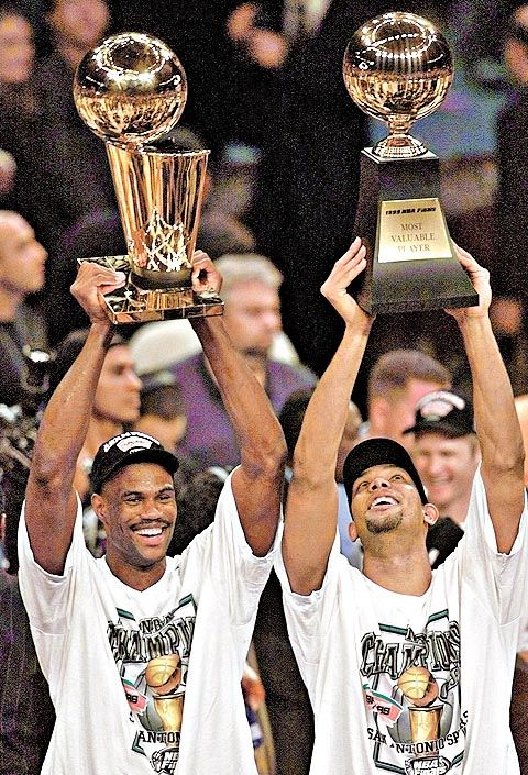 San Antonio Spurs' David Robinson, left, holds up the NBA Championship trophy as teammate Tim Duncan holds up the Most Valuable Player troph