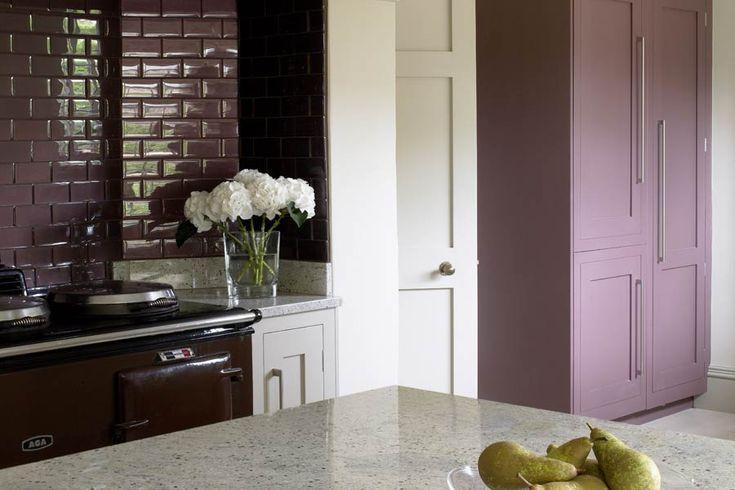 Современный дизайн кухни страны показывает Aga и плитка метро окружает и окрашены сливы цветного шкаф.