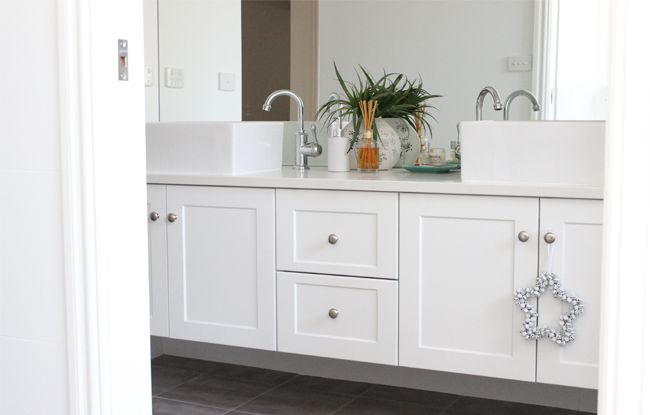 Truly, I love my bathrooms. I had the vanities custom made (to match my kitchen and laundry), and they are perfect. The ensuite bathroom is identical but smaller. The mirrors go all the way to the ceiling. The tops are Osprey Caesar Stone and I love the trough-style sinks. It's pretty basic, but I didn't …