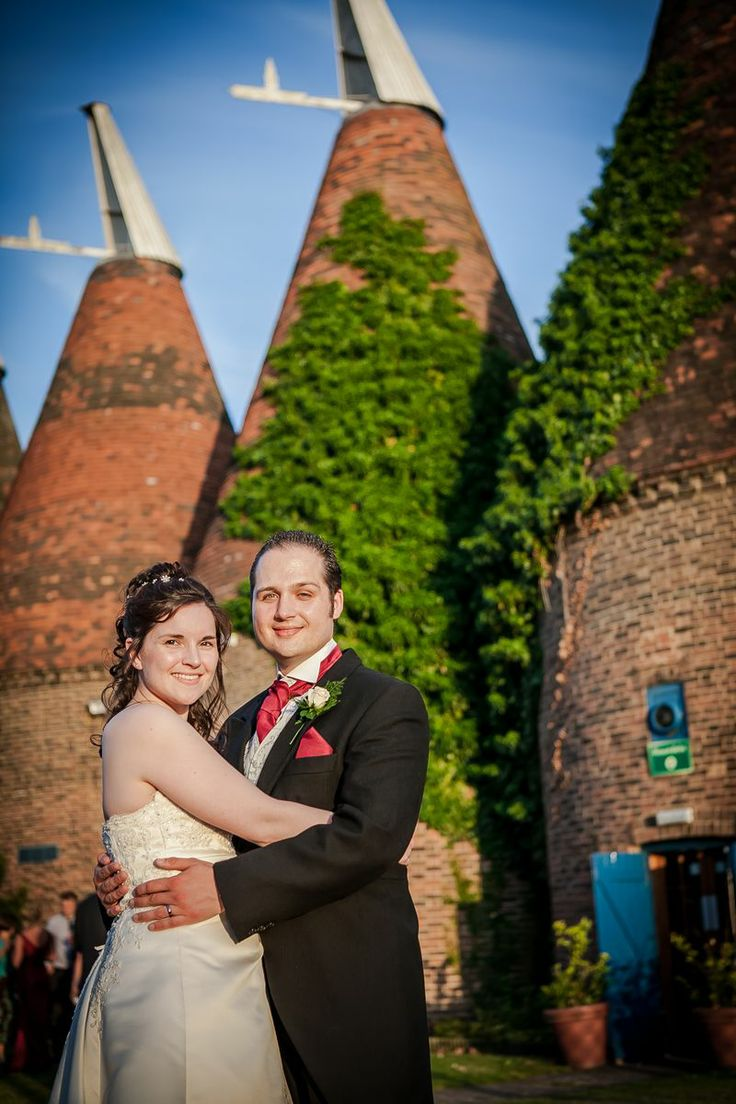 A late evening shot of a bride and groom with oast houses in the background.