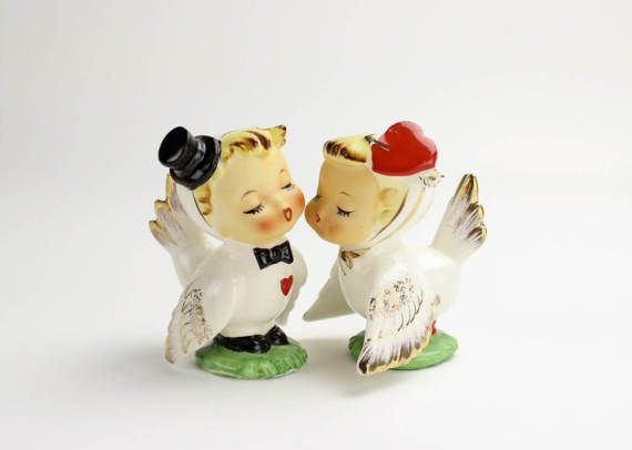 These vintage Napco lovebirds are salt and pepper shakers! Wouldnt they make a lovely cake topper for a wedding? Especially a Valentines Day wedding!  Two little birds are dressed in white with lovely gold touches on their textured wings and upturned tails. Such pretty details! The little boy sports a black top hat and bow tie. He has a little red heart on his chest to declare his love to his sweetheart. The little girl has a darling heart fascinator tied on with a shiny golden ribbon. Love…