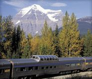 Save 10% off the best available fare on all VIA rail travel.  View of a VIA train in the Rockies.