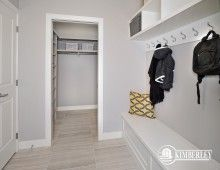 Mudroom, featuring built-in bench and cubbies, and an oversized coats closet for more storage. | The Onyx model Showhome built by Kimberley Homes in Ambleside (Windermere), Edmonton, AB