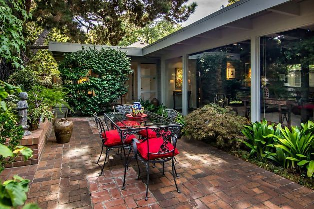 The Palo Alto home includes a private brick courtyard that's visible from inside the home through floor-to-ceiling windows. Photo: Mark Pinker