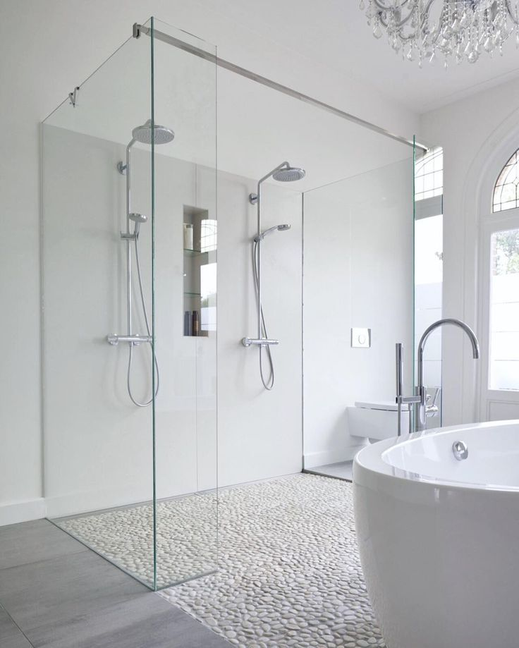 Modern bathroom features a crystal chandelier free standing acrylic tub a mix of marble tile and pebble floor and a double shower with custom made glass panels. by roomporn