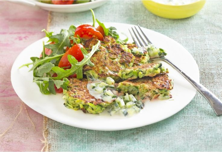 Eat your vegies! These fritters serve up a plate full of zucchini along side a salad with rocket and tomato.