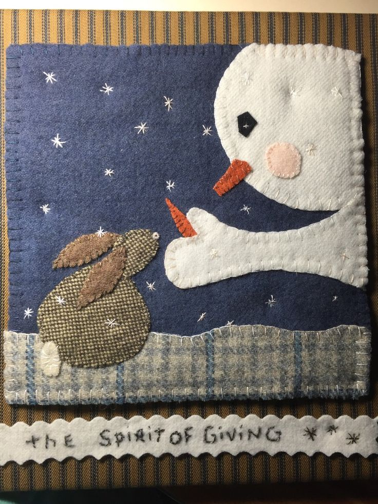 This is a wool appliqué of a snowman sharing his carrot nose with a little bunny. I placed the wool appliqué on a stretched canvas covering