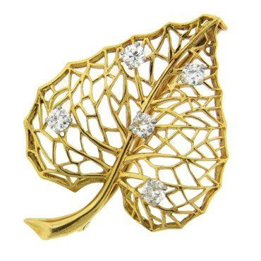 An 18k yellow gold leaf brooch set with approximately 0.70ctw of G/VS diamonds. DESIGNER: Cartier MATERIAL: 18K Gold GEMSTONE: Diamond DIMENSIONS: 40mm x 29mm WEIGHT: 6.9 grams MARKED/TESTED: made in