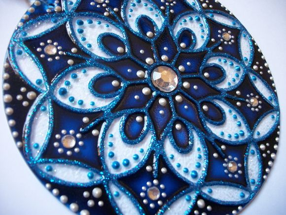 Mandala Móbile em vidro, diâmetro 12cm, técnica pintura vitral impermeabilizada. Decorada com pedras e bolinhas em acrílico, com suporte de nylon e argola segura para pendurar. Embalada em caixa de papelão, protege e é ideal para presente. R$ 39,00