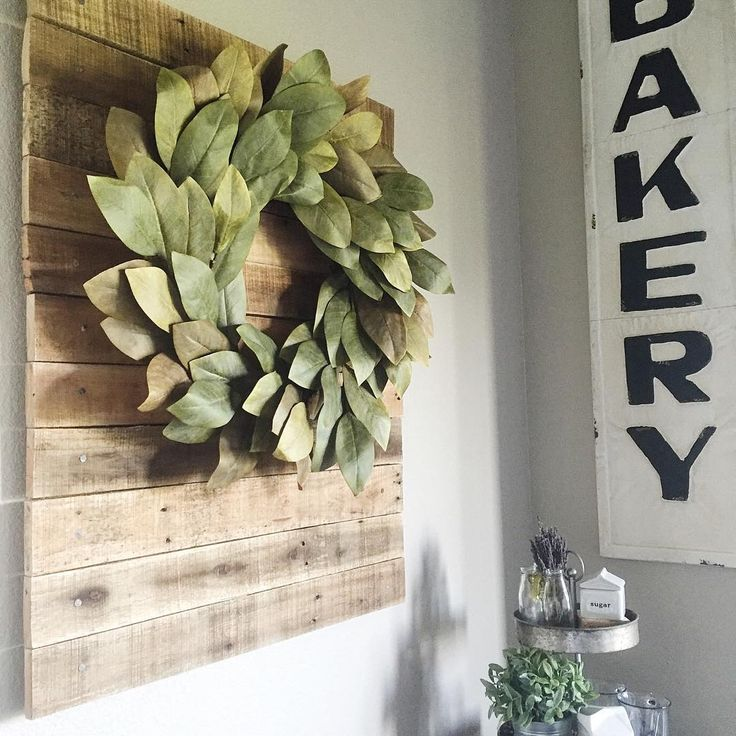 Faux magnolia wreath hung on super simple wood backdrop from leftover pallet wood, bakery sign