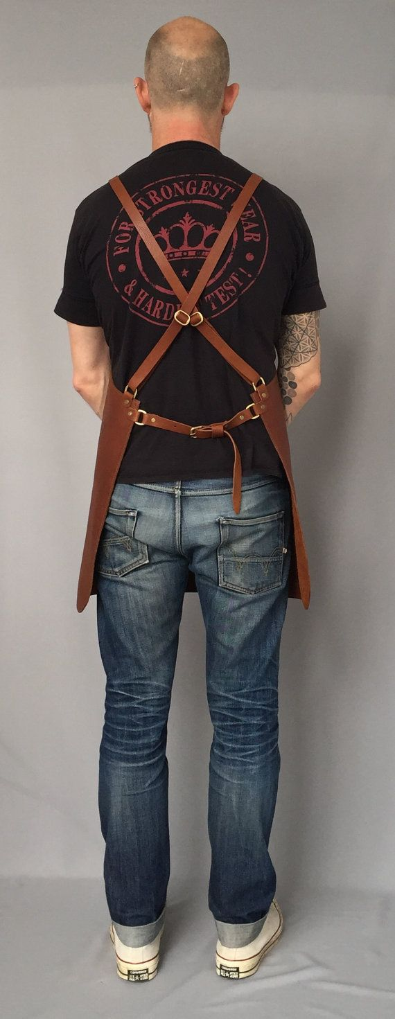 Premium veg tan leather cross back apron created for all types of work.... Chefs apron, cooks apron, butcher apron, tattooist apron, hairstylist apron, barista apron, barber apron.    Tan in colour, supple in texture, this beast of an apron is designed for artisans and artists alike, silversmiths, chefs, barbers, butchers, welders.......  Crafted to fit the body snuggly, with an adjustable cross back strap design. This strap design makes the apron very comfortable to wear for long periods of…
