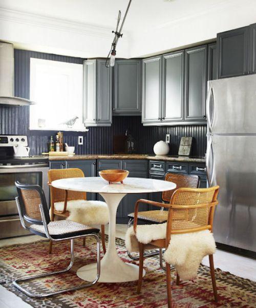 Ruime grijze keuken met eettafel in het midden.